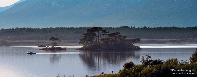 A fishing boat passes islands on shimmering Lough Corrib
