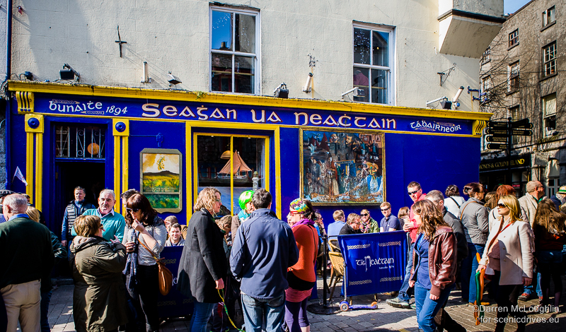 Neachtain's pub Galway on Saint Patrick's Day with people outside the blue and yellow walls